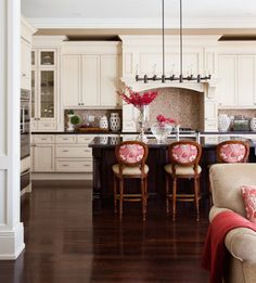 Beautiful kitchen design with white cabinets, a dark wood center island, and dashes of beautiful crimson red.
