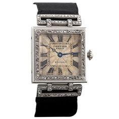 A Cartier Art Deco platinum and 18k gold watch with diamonds. The watch has 117 rose-cut diamonds. The deployant buckle is 18k gold set with diamonds on a silk strap. Circa 1920.