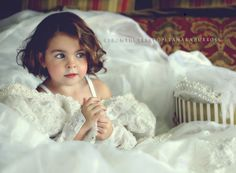 Little girl photographed in moms wedding dress.