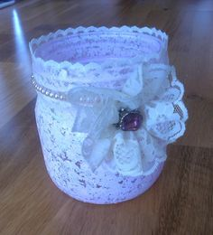 An old jam jar. First I used acryllic paint wich I sponged on. Then I used a lace ribbon around the top, and an old pearl necklace. In the end I took a bigger lace ribbon to make the flower, and a bead in the middle of it. MN