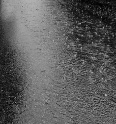 Raindrops Falling From the Sky   photo of raindrops falling on wet pavement with ripples and bubbles