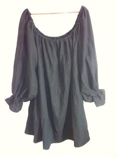 """This is a basic Black Chemise. It is a perfect item for a Women's Renaissance Faire outfit. It is made of linen. It has an elastic collar and cuffs. It is 32"""" long and is available in XLarge. It is made loose and baggy in both the chest and arms, which allows for a wide range of motion and movement."""