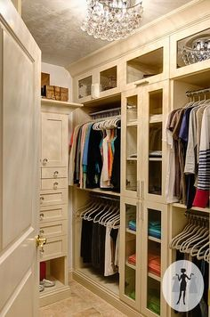 Chic walk-in closet with silver metallic ceiling accented with crystal chandelier as well as floor to ceiling cream cabinets. Closet features glass-front cabinets and accessory cabinet over travertine tiled floor.