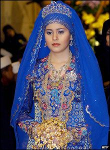 Prince Billah of Brunei's bride Sarah Salleh in her bright blue, embroidered wedding outift, clutching a bouquet made of gold and diamonds.