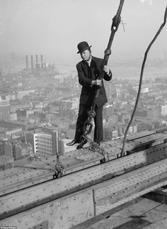Taste of his own medicine: A 1900s cameraman looks a bit unsteady as he hovers one foot over the hedge while walking across steal girders of a skyscraper