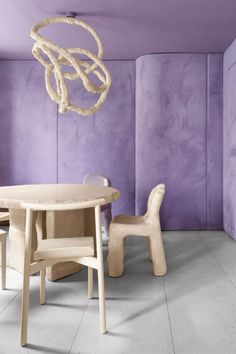 In the second space, the designers explored the visuals of a doughnut's glaze. Walls are covered in plump panels upholstered with berry coloured purple velvet that appears soft to the touch.