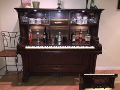 Andy wanted this antique upright grand piano we were trashing due to broken sound board.  Rather he wanted to build a piano bar and here is the final project!!!  With the exception of the backer board all pieces came from stripped off pieces.  The upper lights are dimmable controlled via the pedals and the lower lights come on automatically when the doors are opened.  It really looks awesome with the hanging wine glasses and the hammer board backdrop.  Proud of him and his first major…