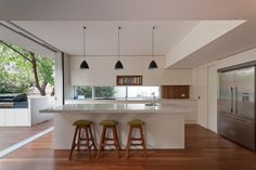 wooden floor, movable wall, large island, window splashback, 3 pendants over island. Could that door be a butlers pantry?