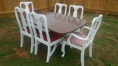 Beautiful Vintage Drop Leaf Kitchen/Dining Room Table w' 6 White Queen Ann Style Chairs. The table is a Duncan Phyfe style table with a newly painted white base. The table top is a mahogany color. The 6 chairs have been newly painted white and all chair cushions have new red fabric. 4 chairs are solid red and the 2 captains chairs are a matching red and white fabric. Great Condition. Designed by Just Tables and Chairs