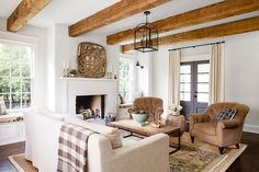Country living room features an earth tone color palette boasting a natural linen slipcovered sofa draped in a gray buffalo check throw facing a pair of brown velvet tufted chairs across from a brickmaker's coffee table atop a brown and blue oushak rug layered over a bound sisal rug.