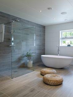 gris perle dans une salle de bain spacieuse avec baignoire blanche en forme ovale