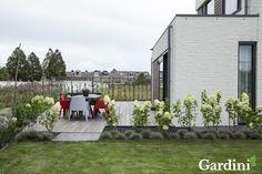 Strakke tuin met eenvoudige beplanting.