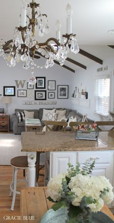 Farmhouse Living Room. Vaulted ceiling with wood beams, gallery wall, vintage chandelier. Home Tour at foxhollowcottage.com - Gracie Blue