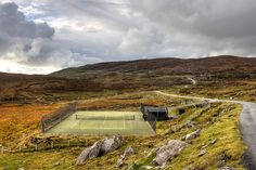Remote Beauty: Nestled among the craggy hills of the Scottish Outer Hebrides, this pristine court is a bright pop against the weathered coastline.