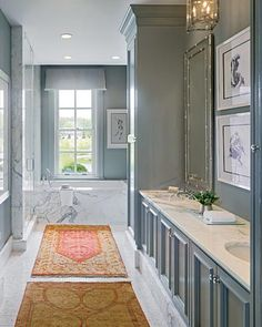The traditionally styled cabinetry painted gray and warm-toned rugs in this bathroom that Gail Plechaty of Real Simple Design created for the 2009 Lake Forest Showhouse & Gardens make it feel almost like a library. The white marble tub and mosaic floor evoke both glamour and a sense of history. The shower and toilet are tucked away behind glass doors on the left.