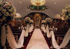 i like the tulle, so people would have to go down the side aisles instead of the center. maybe put the flowers and candles on the opposite side of the pew?