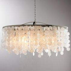 """Modern Capiz Shell Linear Chandelier This beautiful linear chandelier has a Satin Nickel finish to complement rows of dangling Capiz shells. Pair this linear chandelier with modern or transitional home decor pieces for a glamorous look. 5x60 watt medium base lamp. (13.5""""Hx35.75""""W) 15"""" Extension."""