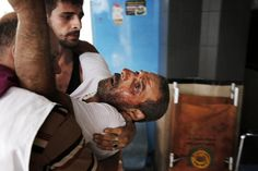 A Palestinian man, who medics said was injured by an explosion during a morning Israeli strike, is carried into Shifa hospital in Gaza City July 19, 2014. Israeli forces on Saturday pressed ahead with a ground offensive in the Gaza Strip, where Palestinian militants kept firing rockets deep into Israel's heartland, pushing the death toll past 300 in almost two weeks of conflict. REUTERS/Finbarr O'Reilly