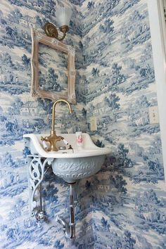 Incredible powder room with Sapphire Blue Toile wallpaper framing a distressed picture frame below a brass and frosted glass wall sconces. Powder Room Wallpaper, Toile Wallpaper, Wallpaper Ideas, Bathroom Wallpaper, Victorian Wallpaper, Framed Wallpaper, Bathroom Art, Bathroom Faucets, Bathroom Ideas