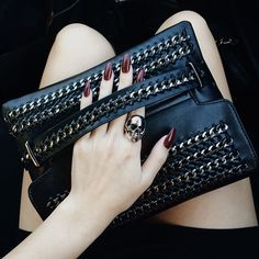 Goth alternative fashion sense black chain clutch with blood dark red almond nails and gold skull ring, pale skin.