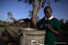 A student treats a vessel of drinking water with Waterguard at Wagai Primary School in Nyanza province, Kenya.