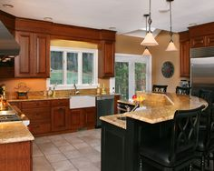 This lovely kitchen expresses emotion through color usage from the warm wall cabinets and base cabinets, to the rich, dramatic island, and the brilliantly bright window trim and flooring.    http://www.topnotchds.com
