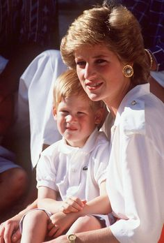 Diana Frances Spencer holding Prince Harry in her lap.