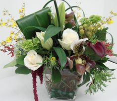 This is a cube vase floral arrangement that features roses, orchids and lilies in a white, green and burgundy.  See our entire selection at www.starflor.com.  To purchase any of our floral selections, as gifts or décor, please call us at 800.520.8999 or visit our e-commerce portal at www.Starbrightnyc.com. This composition of flowers is generally available for same day delivery in New York City (NYC). sq078