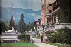 vintage everyday: 27 Rare and Fascinating Color Photographs of Romania in the 1934 - A man stands guard of Castle Peles, with mountains in the background (Sinaia). Castle Window, Flowering Trees, World Cultures, Royalty Free Photos, Romania, Photo Library, Old Photos, 1930s, Around The Worlds