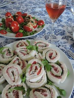 tomatoes stuffed  with couscous, tuna, capers, black olives and mayonnaise / rolled sandwiches with cream cheese, ham, sliced tomatoes and rocket