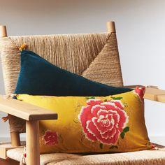Un coussin jaune fleuri Liao en coton et un coussin en velours de coton avec des pompons, Sézane x Caravane