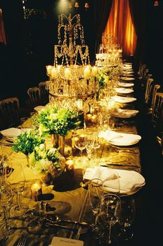 An ornate table chandelier holds eight tealight candles while small votives surround each place setting.