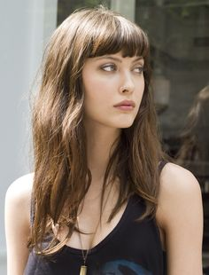 Pretty, simple hair. Thick bangs, kinda messy. Got a little wave. Great face for bangs though.