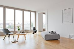 All-white living room with shiny laminate wood flooring and grey Scandinavian style furniture.  7 easy ways to create a summer holiday feel in your home