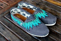 This pair of custom, hand painted Ash Grey canvas classic TOMS shoes features my native American style feather Moccasin design. Blue and green feathers drape down around all sides of the shoes, Hand p