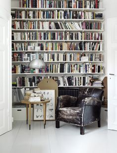 a well stocked book shelf + cozy leather chair.. the perfect pair.