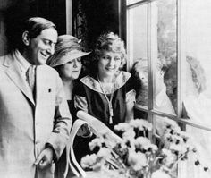 """From chained and perfumed: Charlie Chaplin and Douglas Fairbanks """"press their faces against the glass while Ernst Lubitsch, having recently arrived in Hollywood, poses with Mary Pickford and her mother, Douglas Fairbanks, Mary Pickford, Silent Film Stars, Charlie Chaplin, In Hollywood, Perfume, Poses, Icons, Glass"""