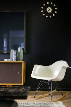 Kontrastreich Fügt Sich Der Weiße RAR Schaukelstuhl In Das Gesamtbild Eines  Raumes Mit Dunklen Wänden Ein
