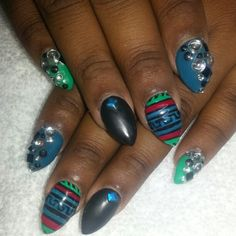 Stiletto nails. Green red blue and black shellac with studs and rhinestones. Aztec designs. Instagram @boop711
