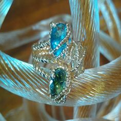 Exquisite caged gem ring Twisted rope detailing with 3 split shank. Three czs blue, yellow, and deep green encaged  and prong setting. Really unique. I honestly don't remember if it's goal over silver, so I'm going to call it goldtone to be safe. This is a true statement ring, I've never seen anything quite like it. Measures at 6.5- 6.75 sizing. Jewelry Rings