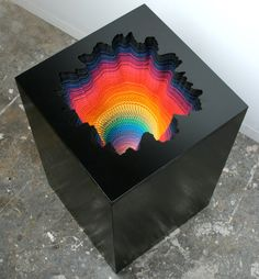 Artist Jen Starck intricately cuts sheets of colored paper and layers them in topographic landscapes or spiraling kaleidoscopes of color.