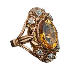 Art Nouveau Citrin, Diamond and Gold Ring. circa 1910  A 14K rose gold ring of an openwork floral design is bezel set with an oval citrin (14.5 x 10 x 6.5 mm, approximately 5 carats) vertically flanked by six gold flowers each prong-set with an old cut diamond (estimated combined diamond weight 0.80 ct).  The ring is marked with later Russian control stamps from the 1930s.