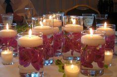 Dulcinéias e Madalenas: Arranjos de mesa econômicos feitos com copos altos, flores artificiais e velas flutuantes
