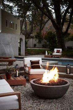 aménagement jardin extérieur avec un foyer, graviers et meubles en bois massif