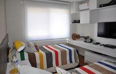 O quarto do Felipe, irmão do Gabriel, tem leves toques de cor no abajur e na roupa de cama. Até o violão entrou na decoração!