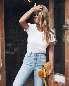 Simple white tee and high waisted jeans, accessorized with a black choke and mustard clutch for a pop of color.