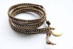 This elegant 4x leather wrap bracelet has a mixed metal look with the metallic kansa leather, bronze faceted Czech beads, and the antique gold closure by Nunn Design. Designed by OneMaker.com.