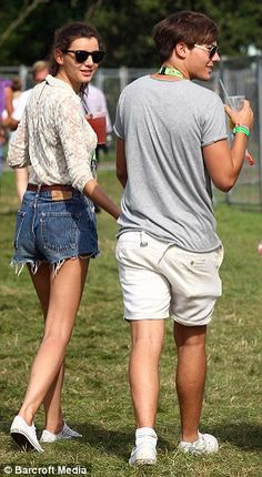 One Direction's Louis Tomlinson and girlfriend Eleanor Calder spent some quality time together at V Festival. They held hands and walked about like true lovebirds. Louis wore a pair of white shorts and a grey printed T-shirt with white trainers. Eleanor showed off her slender figure in a pair of baggy denim shorts, a cream lace blouse and white Converse trainers. via dailymail.co.uk