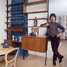 Mick Jagger at home posing with a shelving unit designed by Olaf Pira for String, 1966
