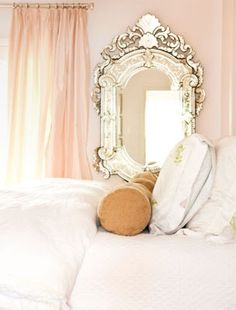 beautiful pale peach bedroom with gilded mirror.